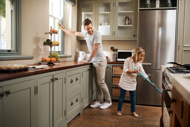 Shot of a young man and his daughter cleaning the kitchen at home